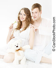 Pregnant happy smiling woman with husband looking at camera. White background.