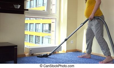 Pregnant house keeper wife woman hoover room with vacuum...