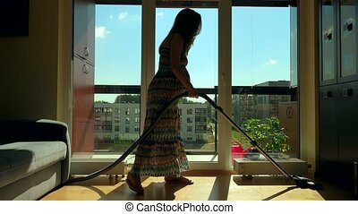 Pregnant house keeper woman with big belly hoover room with...