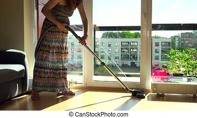 Pregnant house wife with big tummy hoover vacuum clean home