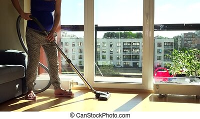 Pregnant house wife with big tummy hoover vacuum clean room in flat house