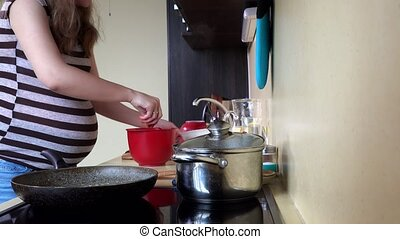 Pregnant house wife woman spice meat and put into cooking...