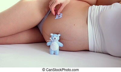 pregnant is the word baby on my belly lying in bed
