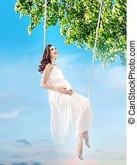 Pregnant lady sitting on the wooden swing