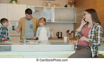 Pregnant lady talking on mobile phone while kids boy and girl doing homework with dad