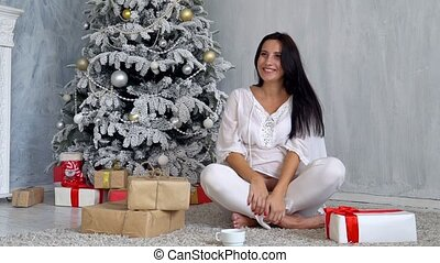 pregnant mom at Christmas tree looking Christmas gifts