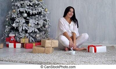 pregnant mom at Christmas tree looking Christmas gifts