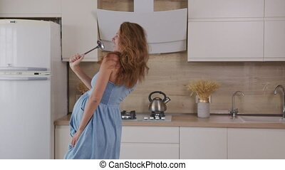 Pregnant Mom Listening Music and dancing at Home at kitchen. Portrait Woman Standing in Kitchen Sunny Day.
