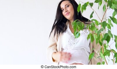pregnant mom smiling stands with green plant