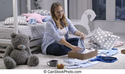 Pregnant mom taking out baby clothes from gift box -...