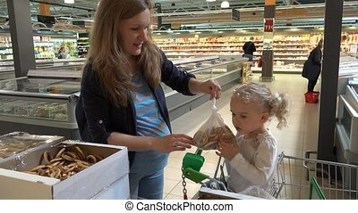 Pregnant mother and adorable girl pick bagel cookies in shopping market