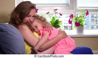 pregnant mother and blond girl care toy baby doll at home....
