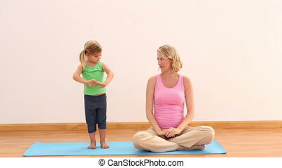 Pregnant mother and daughter doing yoga