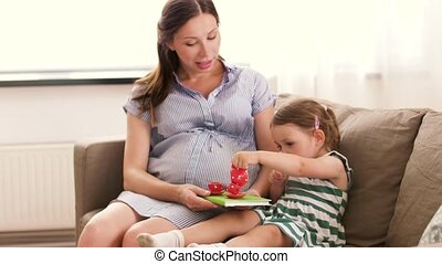 pregnant mother and daughter playing tea party