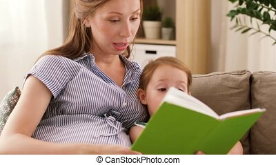 pregnant mother and daughter reading book at home -...