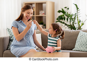 pregnant mother and daughter with piggy bank