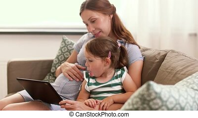 pregnant mother and daughter with tablet pc
