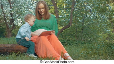 Pregnant mother and son with tablet PC outdoor