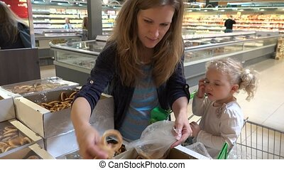 Pregnant mother and toddler girl picking bagel cookies in shopping market