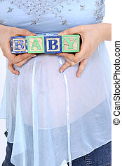 Blocks Spelling Baby Above Expecting Mom's Belly. Shot in studio with the Canon 20D.