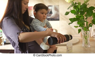 Pregnant Mother cooking with her baby son in the kitchen and having fun - Asian mixed ethnicity child Boy wearing blue body shirt with smiling bear cartoon
