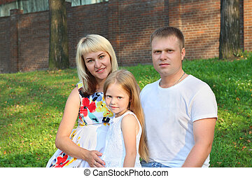 Pregnant mother, father, little daughter pose in summer park