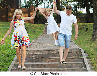 Pregnant mother, father, little daughter walk in summer sunny park