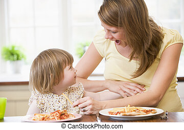 Pregnant mother in kitchen eating chicken and vegetables helping
