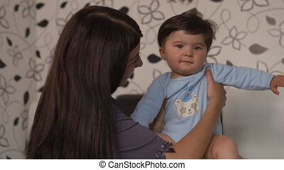 Pregnant Mother laying with her baby son on the bedroom bed playing and having fun - Asian mixed ethnicity child Boy wearing blue body shirt with smiling bear cartoon