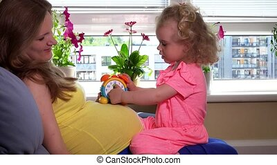 Pregnant mother teaching her cute little daughter girl clock...