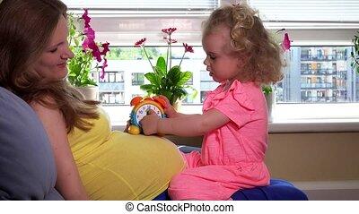 Pregnant mother teaching her cute little daughter girl clock...