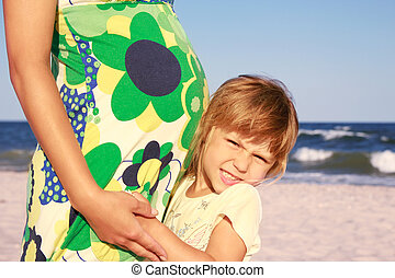Pregnant mother with her daughter playing on the beach