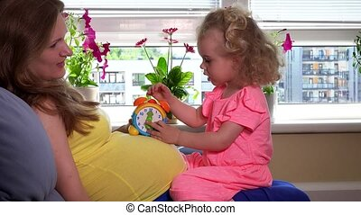 Pregnant mother woman and lovely daughter girl playing with toy clock on stomach