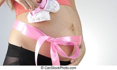 Pregnant mummy in underwear playing with baby booties. belly with pink ribbon