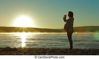 Pregnant on the beach drinking water from a bottle.