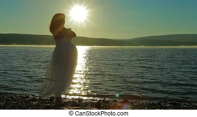 Pregnant on the beach meets the dawn. - A pregnant woman...