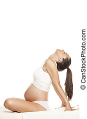 pregnant pretty woman sitting on a bed