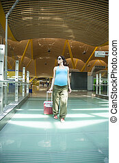 pregnant walking at airport hall