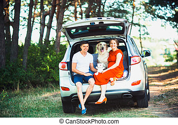 pregnant wife, husband and dog sitting in a car
