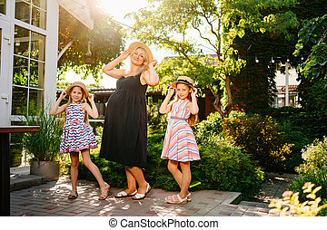 pregnant with daughters in straw hats at sunset
