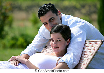 Pregnant woman and boyfriend in the garden
