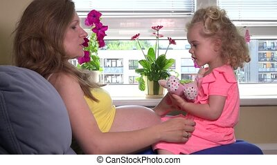 pregnant woman and cute blond girl daughter play with toy baby doll at home
