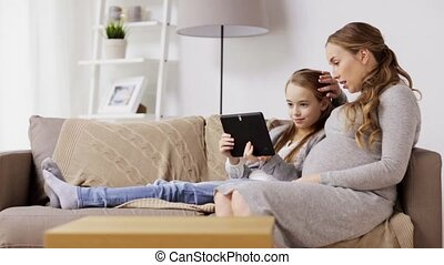 pregnant woman and girl with tablet pc at home