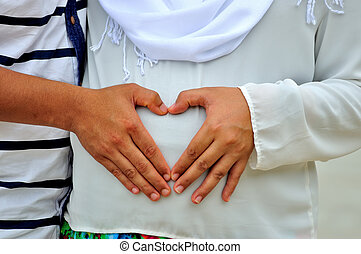 Pregnant Woman and Her Husband holding her hands in a heart shape on her baby bump.