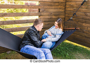 Pregnant woman and man in hammock