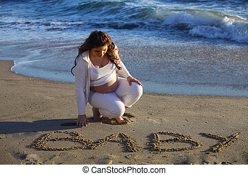 Pregnant woman at beach writing  baby in the sand