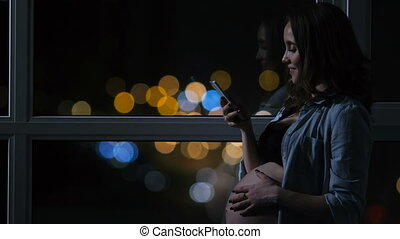 Pregnant woman at night talking on a mobile phone touching his stomach standing at the large panoramic window overlooking the city. Cars drive by outside the window. The girl looks at the phone screen. beautiful bokeh in the background.