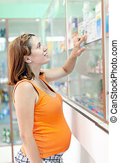 pregnant woman at pharmacy drugstore