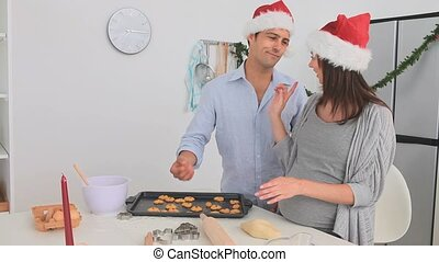 Pregnant woman baking with her husband on Christmas day