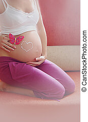 Pregnant woman belly with drawn love sign